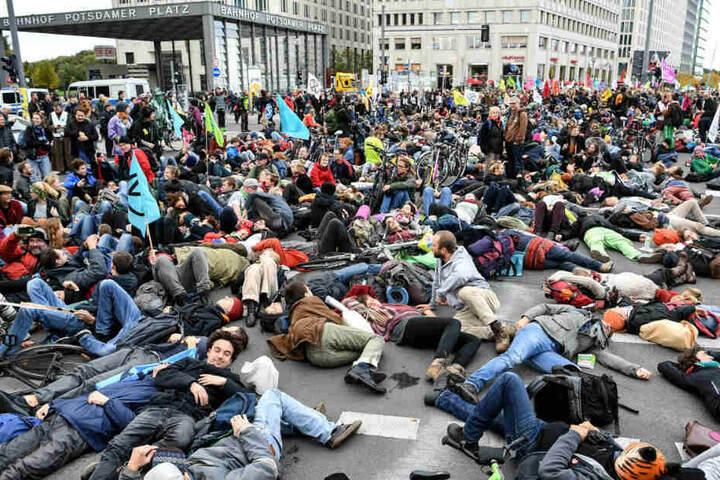 Aktivisten demonstrieren am Potsdamer Platz und legen sich dabei auf den Boden.