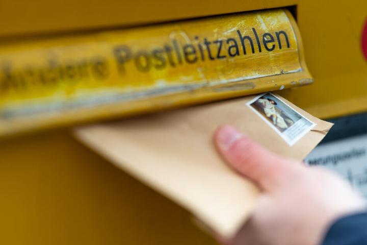 Eine Person wirft einen Briefumschlag in einen Briefkasten. (Symbolbild)