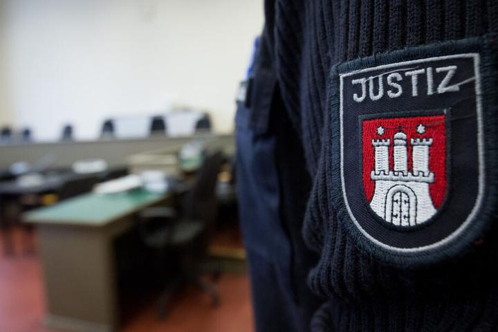 Ein Justizbeamter steht vor der leeren Richterbank im Gerichtssaal im Strafjustizgebäude.