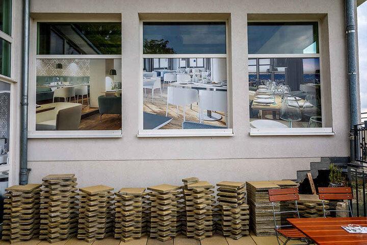 An dieser Seite sind die Fenster des früheren Gastraums mit Fotomotiven verklebt, denn drinnen sieht es nach Baustelle aus.