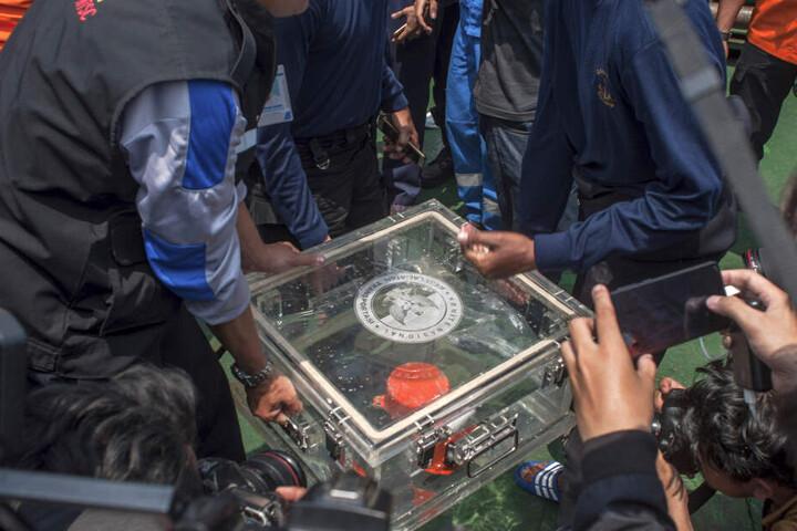 Mitglieder des Nationalen Verkehrssicherheitskomitees heben eine Box mit dem Flugdatenschreiber von der abgestürzten Lion-Air-Maschine an Bord eines Rettungsschiffes.