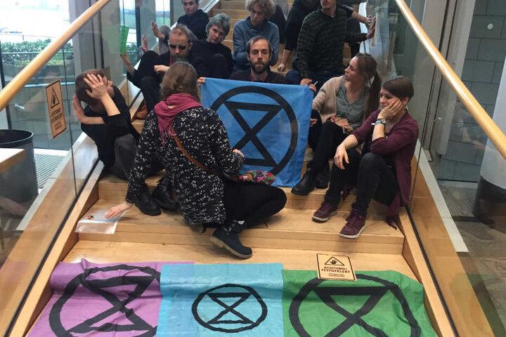 Klimaaktivisten sitzen auf einer Treppe im nordrhein-westfälischen Landtag.