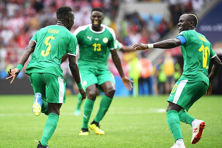 Senegals Kapitän Sadio Mané (r.) und Alfred N'Diaye (M.) bejubeln den Torschützen zum 1:0, Idrissa Gueye (l.).