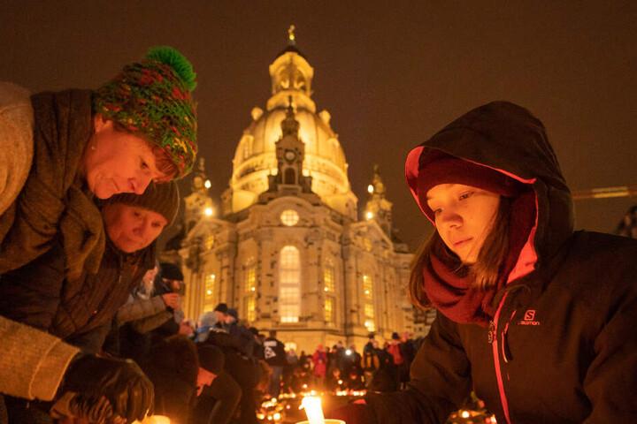 Dresdner zünden auf dem Neumarkt Kerzen an. Im Hintergrund die Frauenkirche.