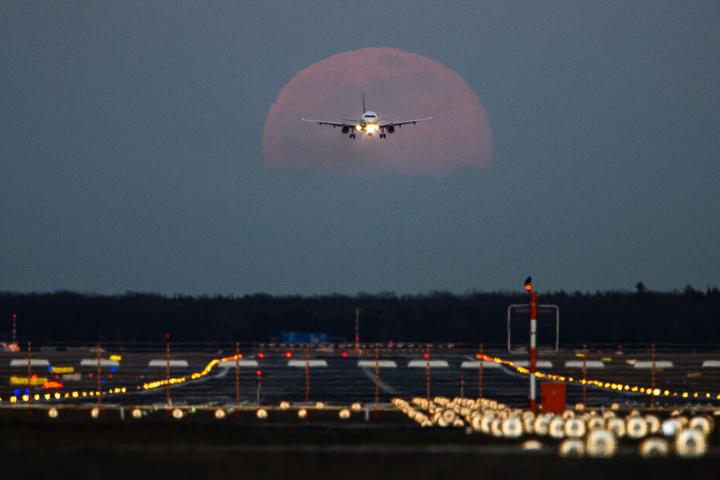 Frankfurt am Main: Ein Passagierflugzeug befindet sich am Frankfurter Flughafen im Landeanflug, während im Hintergrund der Vollmond aufgeht.