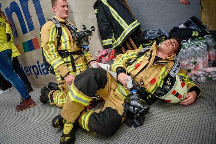 Geschafft aber vollkommen fertig. Zwei Feuerwehrmänner ruhen sich aus, nachdem sie im 39. Stock angekommen sind.