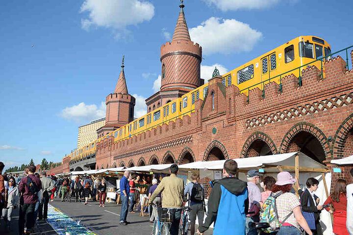 """Besucher sehen sich 2014 auf der Oberbaumbrücke in Berlin bei der Veranstaltung """"Open Air Gallery"""" Kunst an verschiedenen Ständen an."""