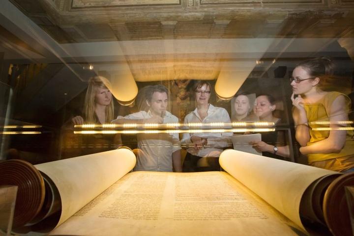 Studenten der Freien Universität Berlin betrachten am 22.06.2012 in der Alten Synagoge Erfurt das Faksimile einer Thorarolle aus dem 13. Jahrhundert.