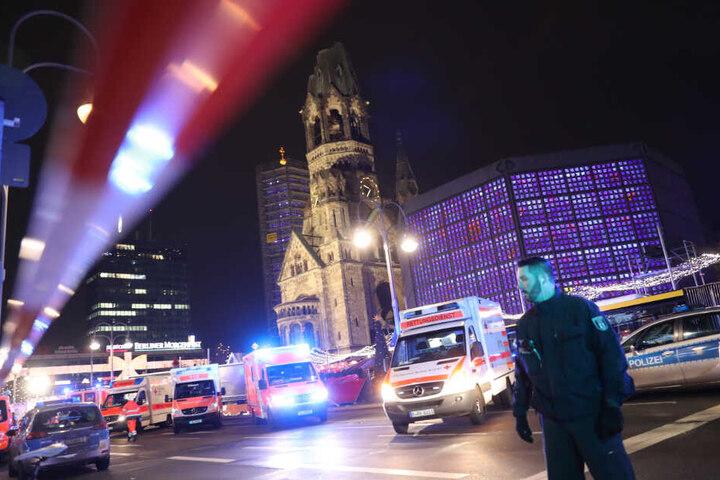 Polizisten und Rettungskräfte stehen vor der Gedächtniskirche in Berlin.