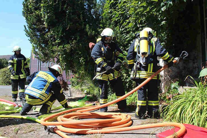 Mit Brecheisen und Wasserschlauch bewaffnet stürmt die Feuerwehr das baufällige Haus.