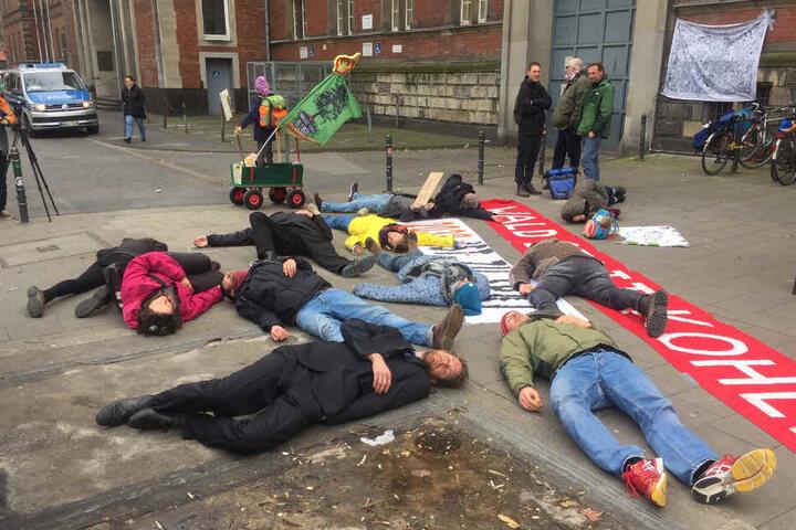 """Aktivisten stellen sich vor dem Verwaltungsgericht tot. Auf dem Banner steht """"Wald statt Kohle""""."""