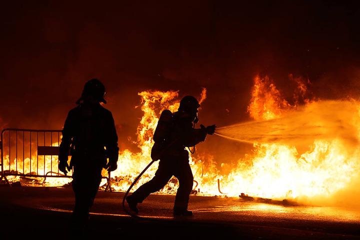 Feuerwehrleute versuchen, in Barcelona eine brennende Straßenbarrikade zu löschen.