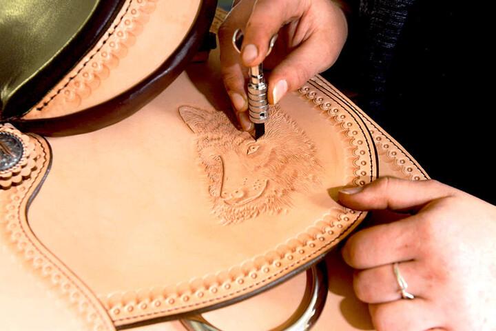 Feinste Handarbeit: Mit einem Punziermesser verziert Theresa einen  Sattel.