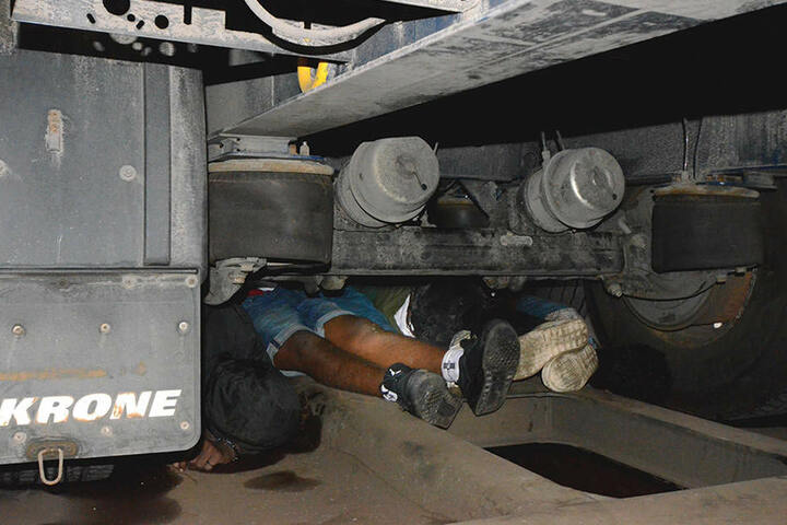 Die Aufnahme zeigt Flüchtlinge, die von der Bundespolizei bei einer Kontrolle eines Güterzuges aus Italien in Raubling (Bayern) unter einem Lkw-Auflieger entdeckt wurden. Insgesamt haben die Beamten auf einem Güterzug zwölf Flüchtlinge entdeckt.