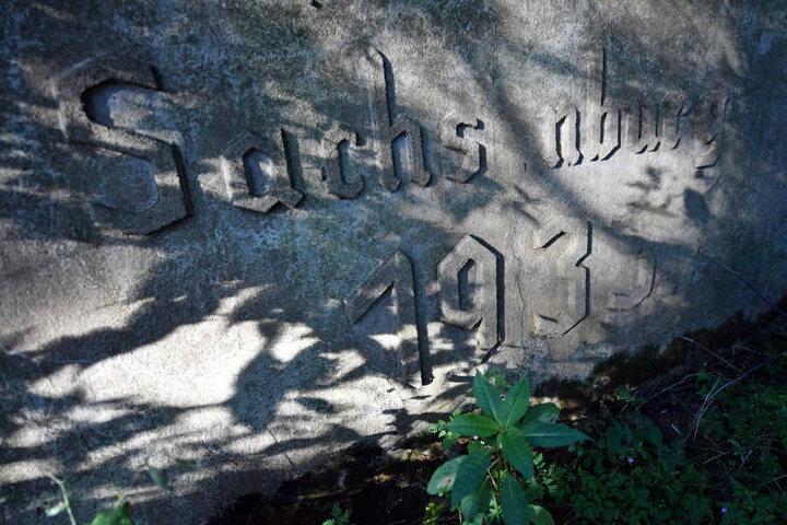 Fragmente einer Inschrift, die einst von Gefangenen des KZ Sachsenburg in Frankenberg (Sachsen), angebracht wurden.