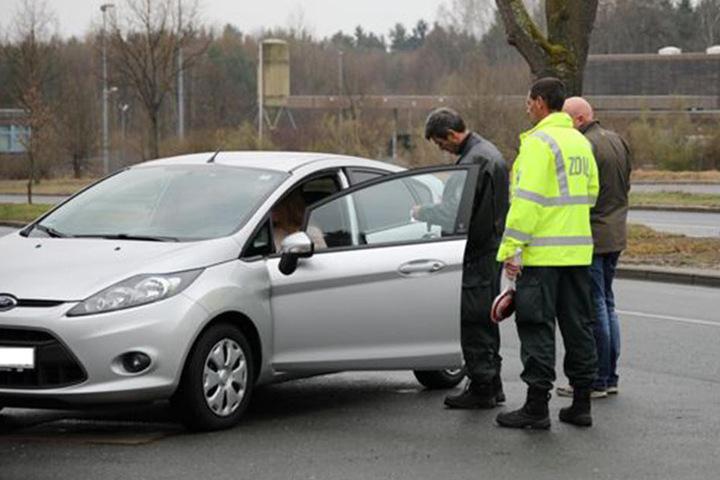 Zoll und Beamte des GFG kontrollieren einen PKW und die Insassen.