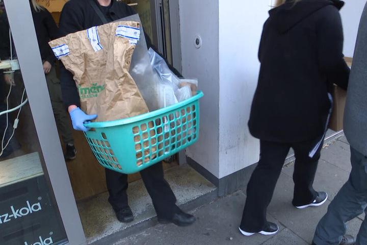 Beamte des LKA tragen beschlagnahmte Ware aus dem Teehaus.