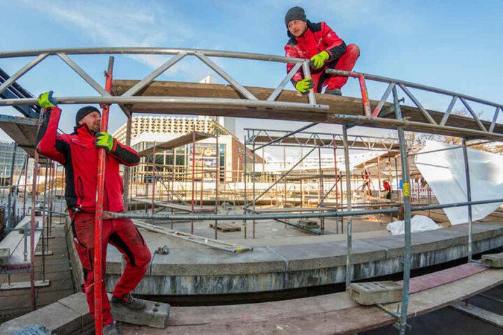 """Kenny Langhans (32, l.) und Roberto Schmieder (32) vom """"Gerüstbau Haustein"""" stellen derzeit das Zelt über dem Stadthallenbrunnen auf."""