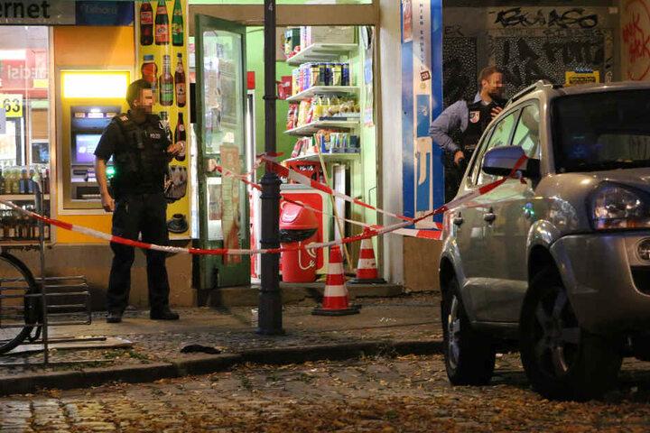 Polizisten mit Maschinenpistolen sichern den Tatort in der Neuköllner Herrfurthstraße ab. Liegen unter den drei rot-weißen Verkehrshütchen die Patronenhülsen?