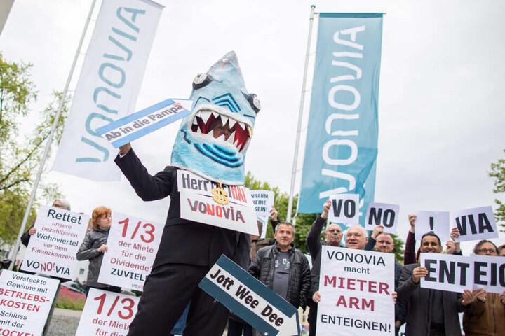 """Ein Demonstrant in einem Hai-Kostüm mit einem Schild um den Hals """"Herr Miethai Vonovia"""" steht vor der Vonovia Hauptversammlung vor dem Ruhrcongress."""