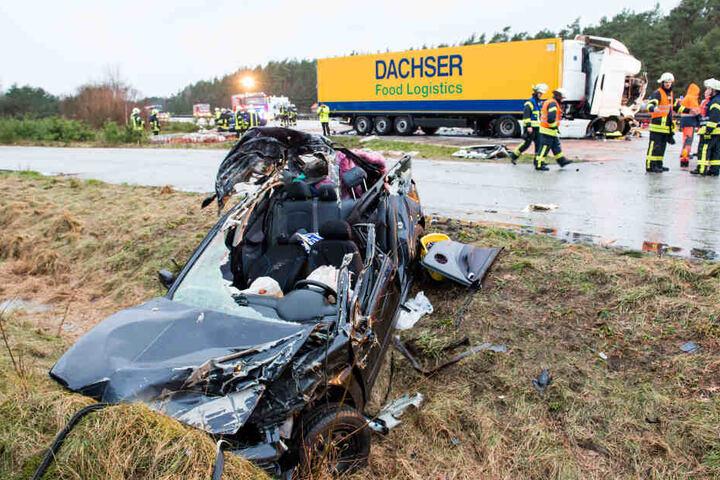 Ein Autowrack liegt neben der Autobahn auf dem Grünstreifen, nach dem es bei dem Unfall mit mehreren Fahrzeugen und einem Viehtransporter komplett zerstört wurde.
