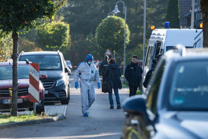 Mitarbeiter der Spurensicherung und der Polizei stehen vor dem Haus, in dem eine Frau bei einem Gewaltverbrechen tödlich verletzt wurde.