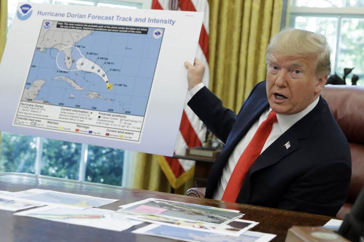 """Donald Trump (73) hält ein Plakat, das den Verlauf des Hurrikans """"Dorian"""" veranschaulicht, während er im Oval Office des Weißen Hauses mit Journalisten spricht."""