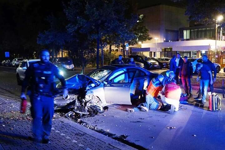 Rettungskräfte kümmern sich um den neben dem Auto liegenden Unfallfahrer.