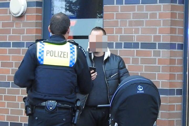 Ein Polizist ermahnt einen Mann, der mit seinem Handy Aufnahmen vor Ort machte.