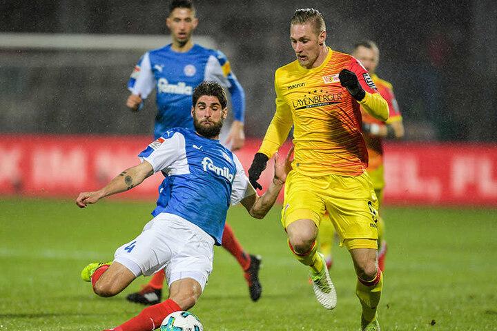 Kiels Niklas Hoheneder (l) und Berlins Sebastian Polter kämpfen um den Ball.