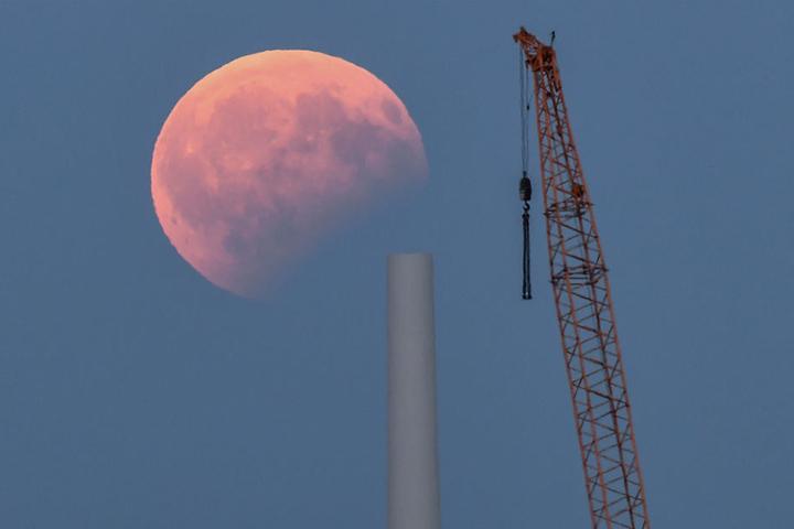 Blick auf die partielle Mondfinsternis über einer Baustelle für eine Windenergieanlage im brandenburgischen Sieversdorf.