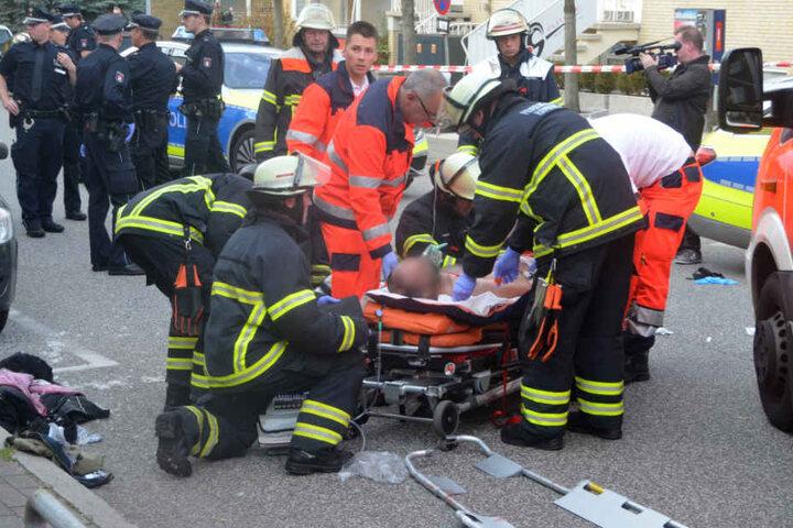 Einsatzkräfte versorgen den verletzten Mann am Tatort.