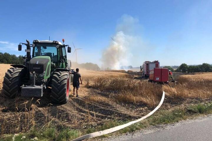 Neben der Feuerwehr ist auch der Landwirt im Einsatz, um seine Ernte zu retten.