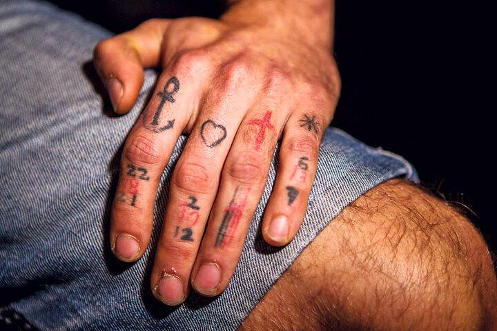 Celiks Finger der linken Hand tragen Symbolen und Zahlen. Die Tattoos stehen für seine ungeborenen und  lebenden Kinder.