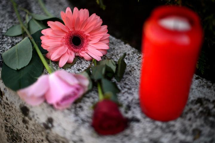 Blumen und ein Grablicht vor dem Haus.