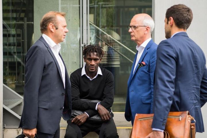 Bakery Jatta (Hamburger SV, 2.v.l.) sitzt neben Bernd Hoffmann (l), Vorstandsvorsitzender des HSV, auf dem DFB-Gelände auf einer Mauer.