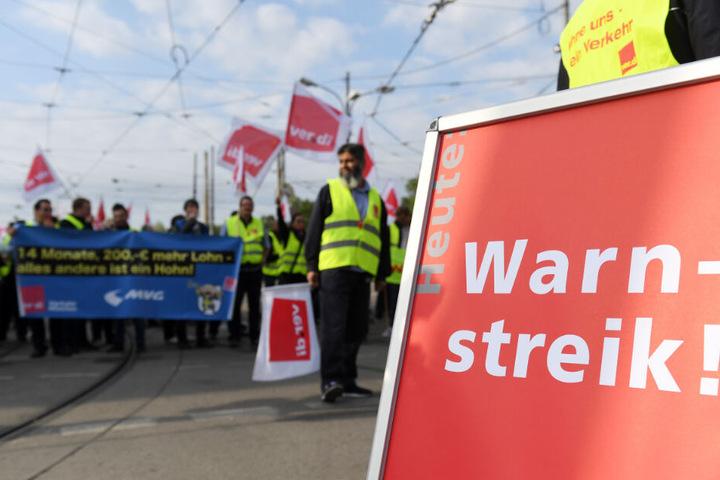 Streikende stehen vor dem Betriebshof in der Einsteinstraße in München und halten Transparente und Fahnen.