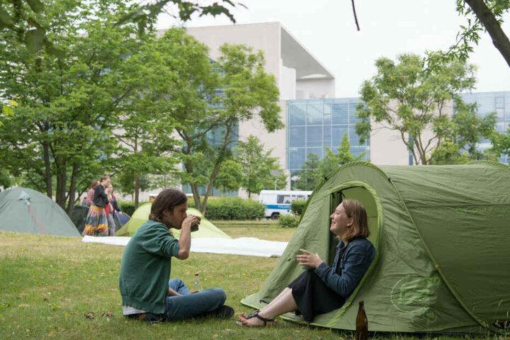 Teilnehmer der Demo sitzen an ihrem Zelt im We4Future-Camp.