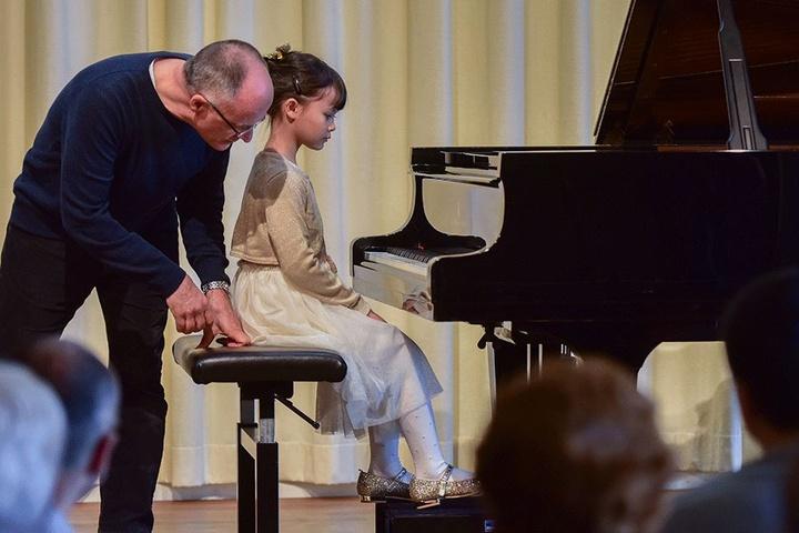 Für die kleinsten Pianisten ist der Flügel noch zu groß. Für Celina kein Problem: Papa Andreas hilft ihr auf die richtige Sitzhöhe.