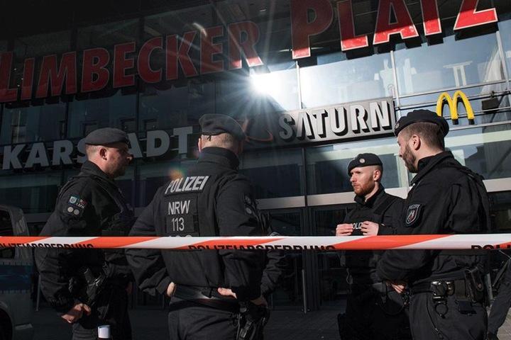 Polizisten stehen vor dem abgesperrte Einkaufszentrum.