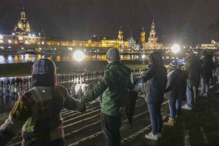 Bürger bilden am Abend vor der historischen Altstadtkulisse eine Menschenkette.
