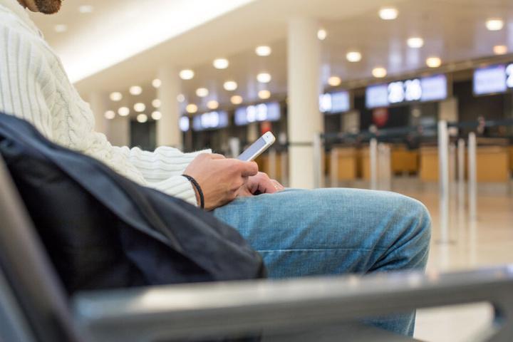 Ein Mann vertreibt sich die Wartezeit am Flughafen mit seinem Smartphone. (Symbolbild)