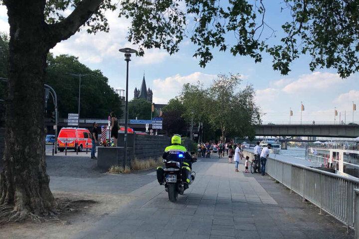 Rettungskräfte suchen das Rheinufer nach einer unbekannten Person ab.
