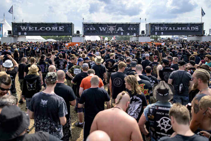 Besucher des Wacken Open Air strömen durch die Eingänge des Festivals auf das Veranstaltungsgelände.