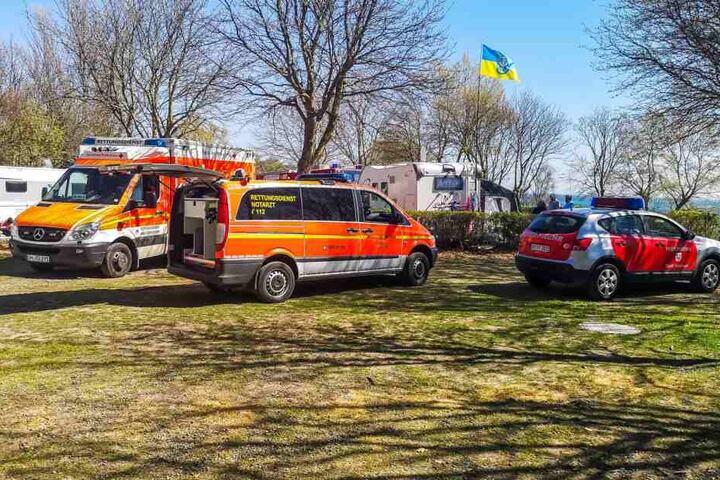 Rettungswagen stehen auf einer Wiese des nahegelegenen Campingplatzes.