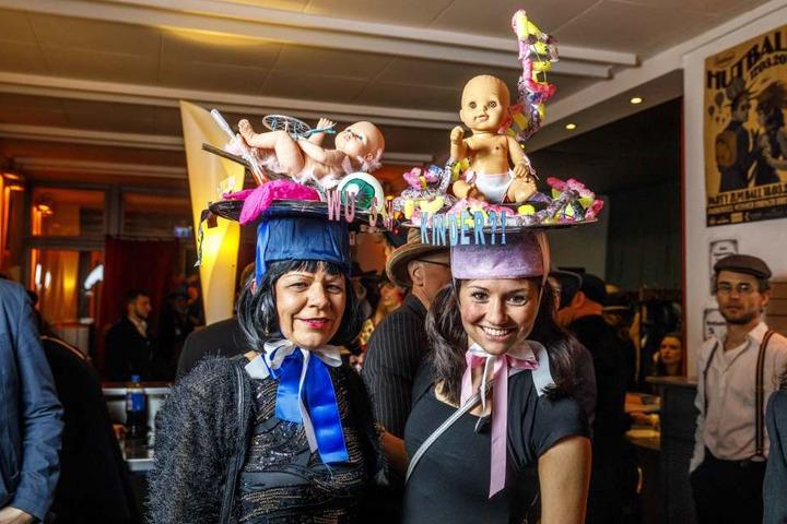 """Sylvia Oehme (53) und Madeleine Polychroniadis (31, r.) installierten auf  ihren Hüten namens """"Wunschkinder!?"""" Babypuppen und DNA-Stränge. Die Hüte des  Duos wurden schon einmal beim Hutball prämiert."""