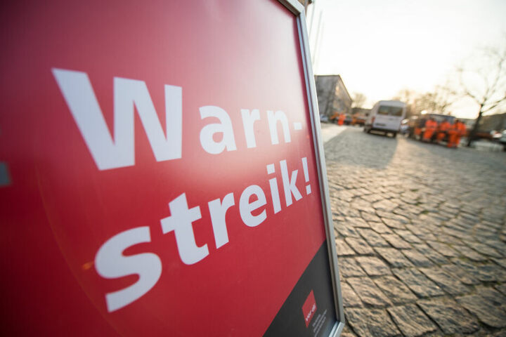 """Ein Schild mit der Aufschrift """"Warnstreik"""" steht auf der Straße. (Archivbild)"""