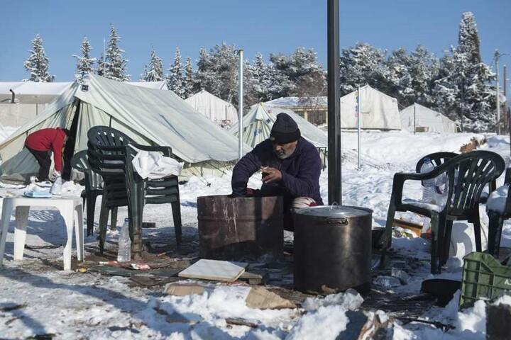 Ein Flüchtling aus Pakistan versucht in einem schneebedeckten Flüchtlingslager nahe des Dorfes Vagiohori, etwa 45 Kilometer östlich von Thessaloniki, Feuer zu entfachen.