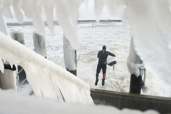 Mit Neoprenanzug wagt sich ein Surfer in die stürmische Ostsee.