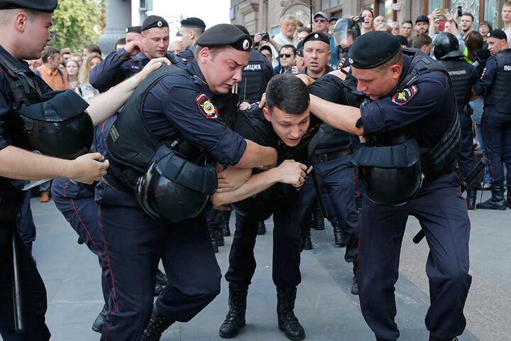 Polizisten halten einen Mann während der Kundgebung im Zentrum von Moskau fest.